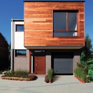 Wśród licznych nowinek technologicznych, nieprzerwanie dobrze ma się drewno naturalne. Ozdobiony nim dom będzie prezentować się szlachetnie i elegancko. A jeśli zestawimy drewniane deski z prostą bryłą i innymi materiałami,  otrzymamy modny, współczesny obrazek. Fot. DLH.