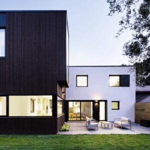 Biały tynk zestawiono z pionową, ciemną deską. Całości nowoczesnego sznytu dodają asymetrycznie rozmieszczone okna. Projekt: Connaught House, Nature Humaine.