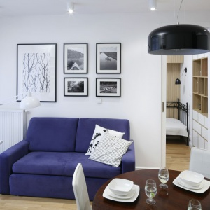 Niebieska sofa wpokoju dziennym stanowi mocny akcent we wnętrzu. Galeria zdjęć na ścianie to prywatna kronika ze spływów kajakowych, które są pasją właścicielki mieszkania. Projekt: Ewa Para. Fot. Bartosz Jarosz.