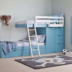 Piętrowe łóżka również mogą zaskakiwać formą. Dolna leżanka wysunięta w bok dała miejsce dla niewielkiej, ale pojemnej szafy na ubrania dziecięce. Fot. Cuckooland.