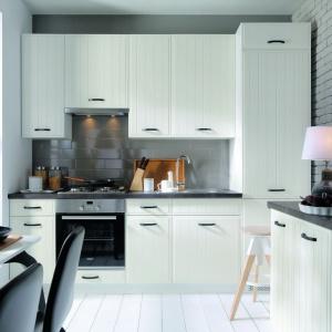 Przytulna kuchnia, łącząca klasyczną i nowoczesną stylistykę. Pionowe frezowania zdobią kuchenne fronty, które wieńczą eleganckie, czarne uchwyty. Ścianę nad blatem zdobią szare kafle. Fot. Black Red White.