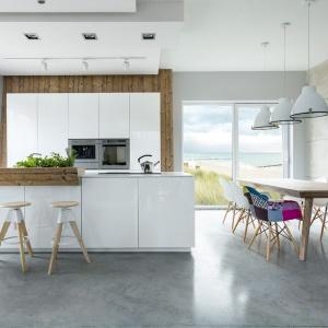 Nowoczesna biała kuchnia ocieplona drewnianymi elementami oraz wyostrzona stylistycznie poprzez zastosowanie industrialnego oświetlenia nad stołem oraz betonu na posadzce i ścianach. Fot. Max Kuchnie.