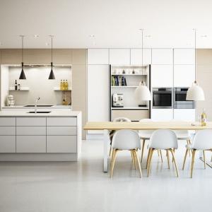 Duże, niczym nieosłonięte okna, biało-drewniana zabudowa kuchenna oraz praktyczny schowek, zaplanowany w wysokiej zabudowie, w którym przechowywać można wszelkie sprzęty i akcesoria. Tak prezentuje się ta nowoczesna kuchnia. Fot. Svane.