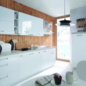Białe meble kuchenne z długim rzędem górnych szafek zestawiono z drewnianymi deskami ułożonymi w pionie, stanowiącymi jednocześnie ścianę nad blatem oraz tło dla zabudowy. Skandynawską atmosferę buduje nie tylko zestawienie drewna z bielą, ale również oświetlenie oraz okno bez firan i zasłon. Fot. Black Red White.