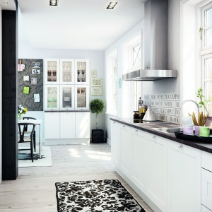Białe meble kuchenne, zwieńczone blatem w ciemnym kolorze drewna zestawiono z dekoracyjnymi płytkami z motywem napisów. Akcesoria i sprzęty można schować za przeszklonymi frontami regału, uzupełniającego wyposażenie kuchni. Okna obowiązkowo pozbawione firan. Fot. HTH.
