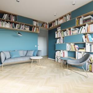 Zabudowa w strefie salonu została zaplanowana tak, aby liczne półki mogły pomieścić duże ilości książek, funkcjonując jako pojemna biblioteczka. Projekt i wizualizacje: 081 Architekci.