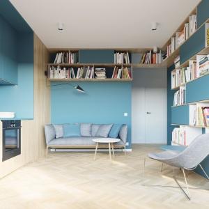 Strefę dzienną stanowi aneks kuchenny, poprowadzony wzdłuż całej ściany, niewielki salonik oraz usytuowany pod oknem gabinet. Projekt i wizualizacje: 081 Architekci.