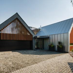 Blachę na rąbek stojący, pokrywającą dach oraz boczne ściany domu zestawiono z ażurowymi elementami drewnianymi zyskując intrygujący efekt. Projekt: Dwie Stodoły, RS+ architekci. Fot. Tomasz Zakrzewski / archifolio.pl