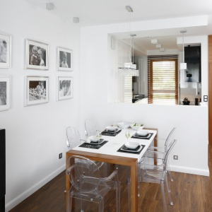 W przeciwieństwie do salonu przestrzeń kuchni jest jasna. Ubrana w biel rozjaśnia całe wnętrze. Projekt: Michał Mikołajczak. Fot. Bartosz Jarosz.