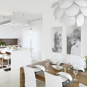 Elegancka kuchnia, w której zestawiono ze sobą śnieżną biel z rysunkiem poziomych słojów drewna otwiera się na jadalnię, od której symbolicznie oddziela ją wyspa, pełniąca rolę kuchennego baru. Projekt: Agnieszka Ludwinowska. Fot. Bartosz Jarosz.
