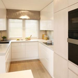 Zabudowę poprowadzoną w głąb kuchni wykończono lakierem w wysokim połysku w kolorze złamanej bieli. Projekt: Małgorzata Galewska. Fot. Bartosz Jarosz.