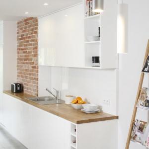 Zabudowę kuchenną utrzymano w białym kolorze, którego sterylność ociepla drewniany blat oraz czerwona cegła na ścianie. Projekt: Agata Piltz. Fot. Bartosz Jarosz.