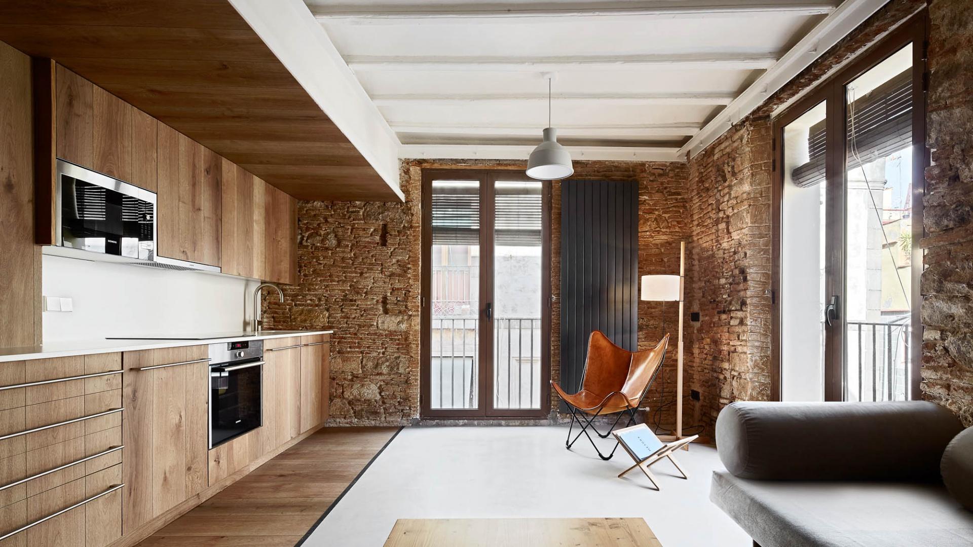 Apartamenty urządzono w przytulnym, rustykalnym stylu. Jednym z charakterystycznych elementów wystroju jest naturalny kamień na ścianach. Projekt: MESURA, Partners in Architecture. Fot. José Hevia.