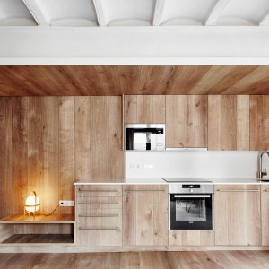 Architekci we wszystkich apartamentach bardzo chętnie sięgali po drewno - jest ono obecne na frontach mebli, jak i na ścianach. Jego ciepłe wybarwienie  idealnie współgra z kamieniem na ścianie. Projekt: MESURA, Partners in Architecture. Fot. José Hevia.