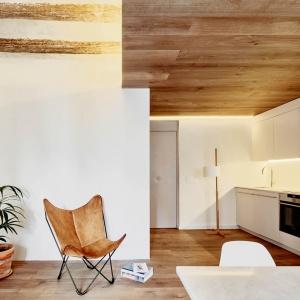 W przestrzeniach, gdzie meble są utrzymane w złamanym kolorze bieli postawiono na drewnianą podłogę i... sufit. Projekt: MESURA, Partners in Architecture. Fot. José Hevia.