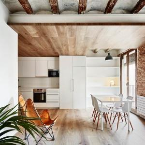 Sufit podkreślają widoczne belki stropowe - niekiedy mocniej wyeksponowane, innym razem pomalowane na biało, ale wciąż zaznaczone. Tutaj ich obecność podkreśla ciemny kolor drewna. Projekt: MESURA, Partners in Architecture. Fot. José Hevia.
