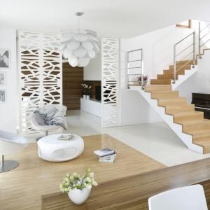 W otwartym salonie dominuje biel, w tym też kolorze są dekoracyjne lampy, które umieszczono w rożnych strefach użytkowych. Projekt: Agnieszka Ludwinowska. Fot. Bartosz Jarosz.