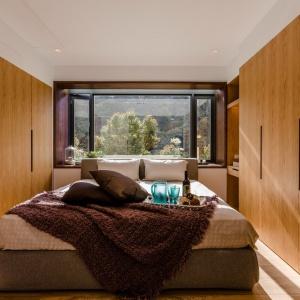 Sypialnia jest bardzo przytulna za sprawą wysokiej zabudowy pokrywającej ściany, której fronty wykończono w naturalnym drewnie. Projekt i zdjęcia: Archlin Studio.