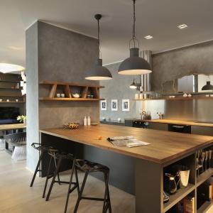 Kuchnię urządzono w nowoczesnym stylu loft. Szara ściana imituje beton, gładkie matowe fronty w ciemnoszarym kolorze wieńczy drewniany blat, a na podłodze położono posadzkę z bielonego drewna. Projekt: Gao Arhitekti. Fot. Miran Kambic.