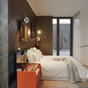 W sypialni ciemnoszarą ścianę z przecieranym efektem dekoracyjnym zestawiono z drewnianą podłogą w ciepłym kolorze. Projekt: Gao Arhitekti. Fot. Miran Kambic.