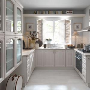 Bardzo kobieca kuchnia w kolorze złamanej bieli jest idealnym przykładem na uniwersalną aranżację w delikatnie prowansalskiej estetyce. Fronty mebli są frezowane, niektóre przeszklone, zwieńczone metalowymi, okrągłymi uchwytami. Fot. Black Red White.