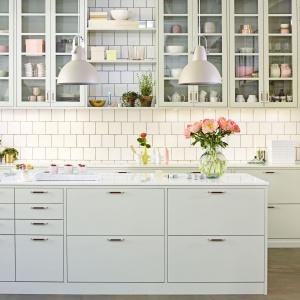 Nowoczesna wariacja na temat kuchni w stylu prowansalskim. Gładkie fronty mebli kuchennych utrzymano w bladym, niebieskawym odcieniu, górne szafki zdobią symetryczne przeszklenia. Całości dopełniają świeże kwiaty. Fot. Ballingslov.