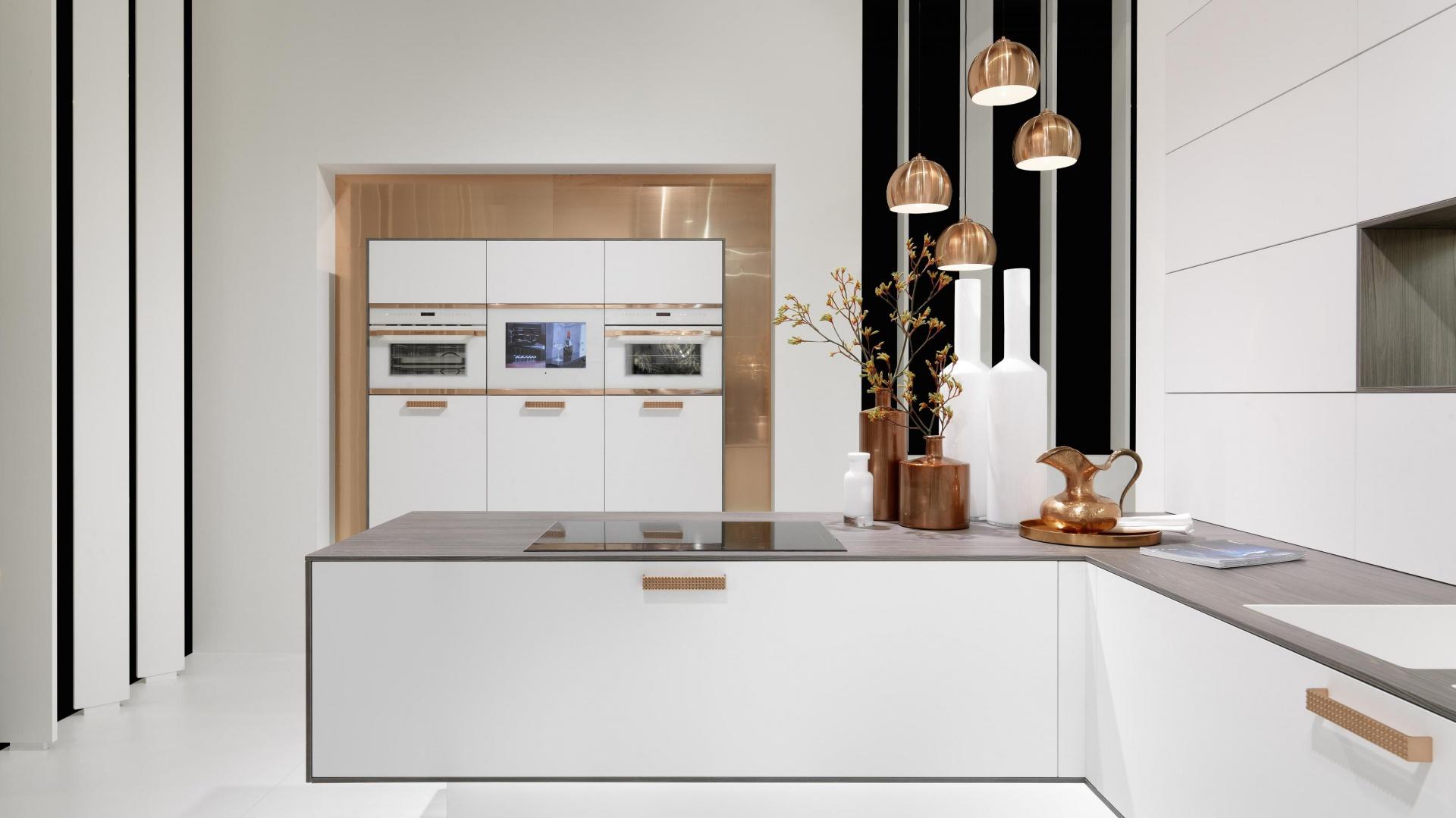 Biała odsłona pięknej, odważnej kuchni, w której główną gwiazdą jest złoto. Tutaj jego kolor obecny w formie powierzchni za wysoką zabudową oraz jako eleganckie, duże uchwyty wieńczące fronty zabudowy kuchennej. Dodatkiem są półokrągłe lampy w złotym kolorze. Fot. Rational, model Topaz.