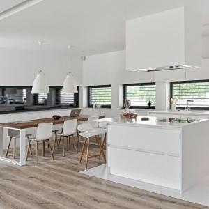 Wyspa kuchenna stanęła na granicy kuchni z jadalnią, zaznaczonej dodatkowo innym wykończeniem podłogi. Fot. Atlas Kuchnie, model Oktawia Listwowy.