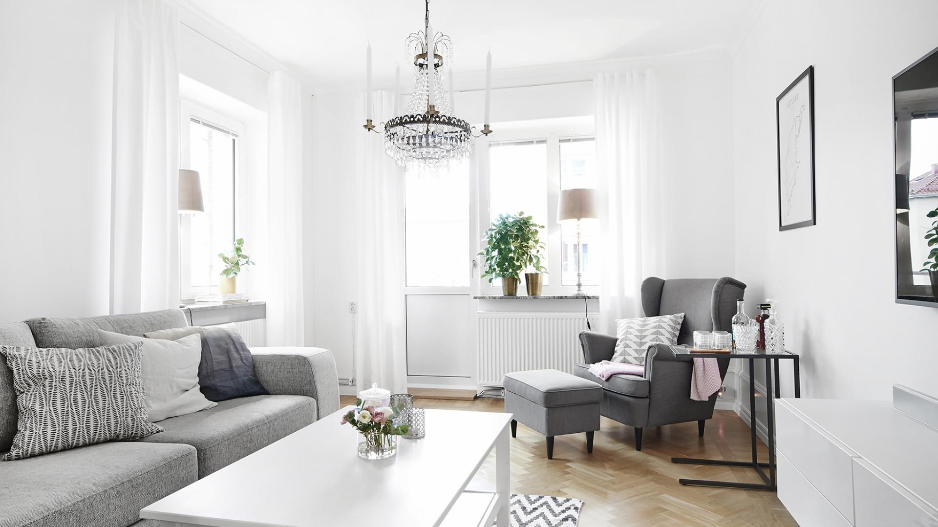 Salon z oknami wychodzącymi na południe jest rozświetlony naturalnym światłem, odbijającym się od pomalowanych na biało ścian. Królowanie bieli równoważą szarości i drewno na podłodze. Fot. Vastanhem.se.