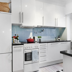 Ścianę nad blatem w kuchni wykończono symetrycznymi glazurowanymi płytkami w bladoniebieskim kolorze. Przełamano w ten sposób duet bieli i czerni. Fot. Vastanhem.se.