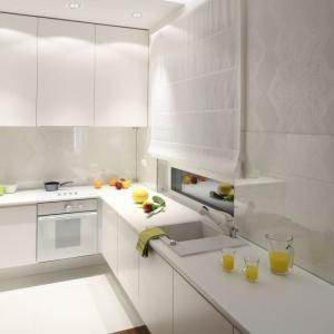 Urządzenie kuchni całkowicie w bieli pozwoliło optycznie powiększyć wnętrze. Wysoka zabudowa na jednej ścianie oraz górne szafki poprowadzone pod sufit ułatwiają przechowywanie sprzętów. Blat kuchenny jest bardzo długi, mimo iż kuchnię wpasowano w niewielką wnękę. Dzieje się tak za sprawą przedłużenia dolnej zabudowy poza przestrzeń wnęki. Projekt: Katarzyna Merta-Korzniakow. Fot. Bartosz Jarosz.