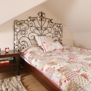 Wpasowane w niszę pod skosami łóżko zachwyca pięknym, zdobnym, kutym ogrodzeniem, które dodatkowo udekorowano fikuśnymi lampkami. Projekt: Piotr Stanisz. Fot. Bartosz Jarosz.