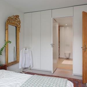 Zbudowanie garderoby na ścianie, na której są drzwi wejściowe do sypialni to dobry pomysł do małego pokoju. Dzięki zabudowie pod sam sufit wiele się w niej zmieści. Fot. Alvhem Makleri.
