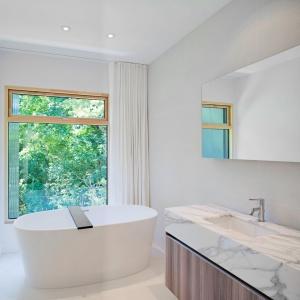 Łazienka z oknem, za sprawą wolno stojącej wanny z widokiem na otoczenie oraz kamiennego blatu, ma charakter luksusowego salonu kąpielowego. Projekt: TACT Design. Fot. David Giral.