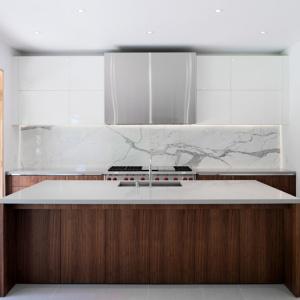 Korpusy wyspy i dolną zabudowę kuchenną wykończono w drewnie, natomiast górne szafki są białe, gładkie i połyskujące - ultra nowoczesne. Obie powierzchnie pogodził jasny kamień nad blatem. Projekt: TACT Design. Fot. David Giral.