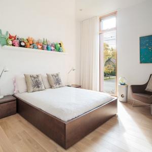 W domu wszystkie pomieszczenia są urządzone w jasnych kolorach. Wyjątkiem nie jest sypialnia, w której stanęło duże łóżko z towarzyszącymi mu drewnianymi szafkami nocnymi na tle białych ścian. Projekt: TACT Design. Fot. David Giral.