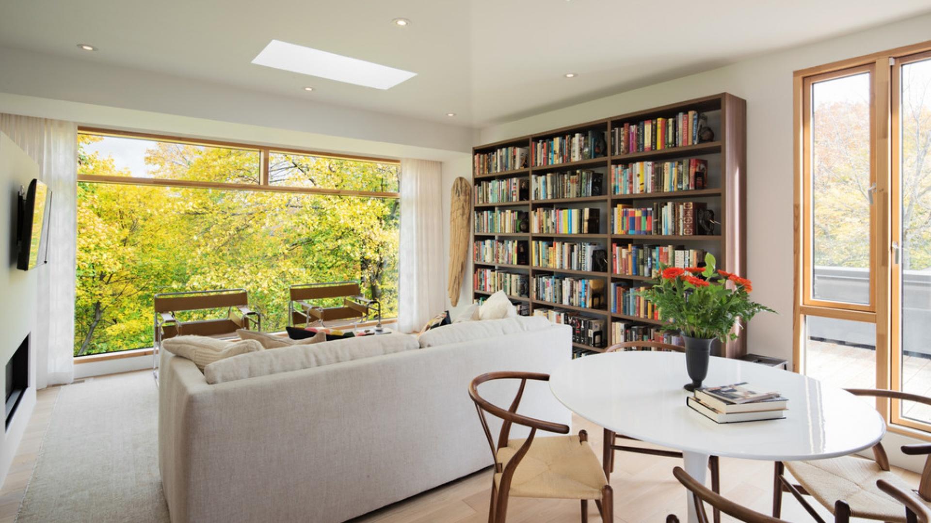 Jedną ze ścian w salonie pokrywa duża, drewniana biblioteczka, harmonizująca z krzesłami, wykonanymi z giętego drewna. Projekt: TACT Design. Fot. David Giral.