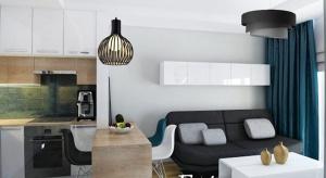 Wnętrze jest bardzo dobrze doświetlone dzięki dużym oknom. Meble do salonu i kuchni wykonano w bieli w połysku, natomiast kontrastu dodają sofa, fotele oraz długie ciemne firany.