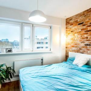 W sypialni postawiono na nieco bardziej spokojną kolorystykę. Prym wiedzie tutaj czerwona cegła na ścianie, przy której stanęło łóżko. Błękit można tutaj jednak wprowadzić przy pomocy tekstyliów na łóżku. Projekt:  COCO Pracownia projektowania wnętrz. Fot. Łukasz Markowicz.