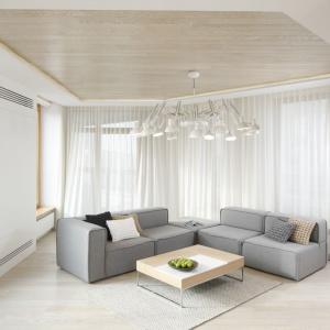 Elegancki salon urządzono w bieli i szarości. Ograniczone do minimum wyposażenie podkreśla jego minimalistyczny styl. Całość ociepla drewno. Projekt: Maciej Brzostek. Fot. Bartosz Jarosz.