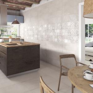 W aranżacji tej kuchni postawiono na patchworkowe wzory w harmonizującej barwie bladej szarości. Dzięki temu mozaika motywów nie przytłoczyła aranżacji kuchni, jest jedynie subtelnym akcentem w stonowanej przestrzeni. Fot. Ibero Ceramica, płytki z serii Maison.