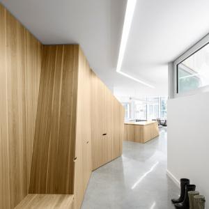 Podążając za drewnianą zabudową, która wita domowników i gości już w holu budynku, dotrzemy do strefy dziennej, usytuowanej w jednym rzędzie z przedpokojem. Projekt: Paul Bernier architecte. Fot. Adrien Williams.