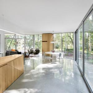 Ogromne, panoramiczne przeszklenia stanowią znaczną część elewacji budynku. Są również pełnoprawnym elementem aranżacji wnętrza. Nie tylko wprowadzają do domu światło, ale także zapraszają do środka naturę. Projekt: Paul Bernier architecte. Fot. Adrien Williams.
