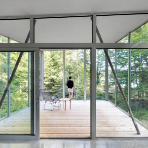 W domu zaplanowano całkowicie przeszklony kącik wypoczynkowy. W lecie cień dają tutaj otaczające dom drzewa, zimą wpadające przez okna słońce dogrzewa dom. Projekt: Paul Bernier architecte. Fot. Adrien Williams.