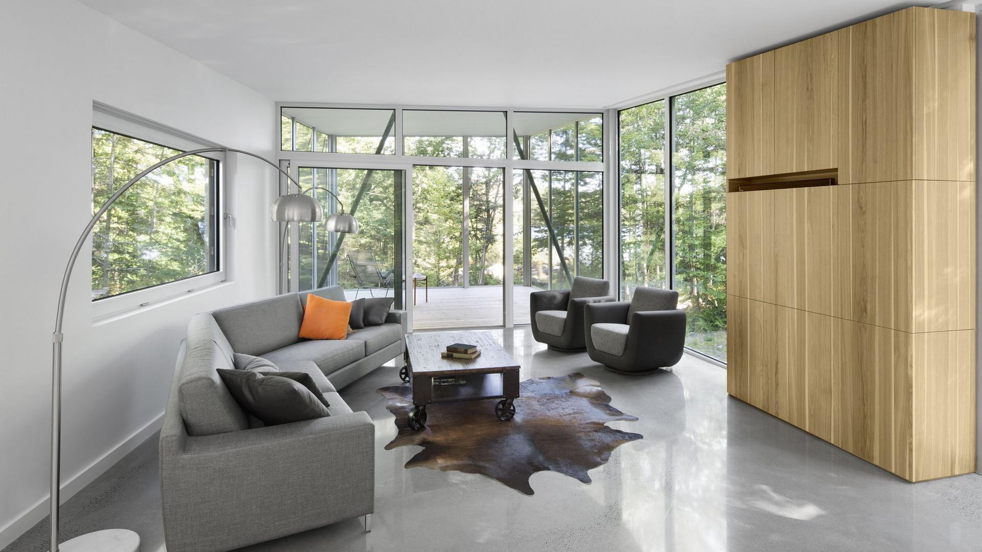 Połączenie szkła w formie ogromnych okien, betonu na podłogach oraz naturalnego drewna zabudowy meblowej tworzy elegancką, nowoczesną kompozycję. Projekt: Paul Bernier architecte. Fot. Adrien Williams.