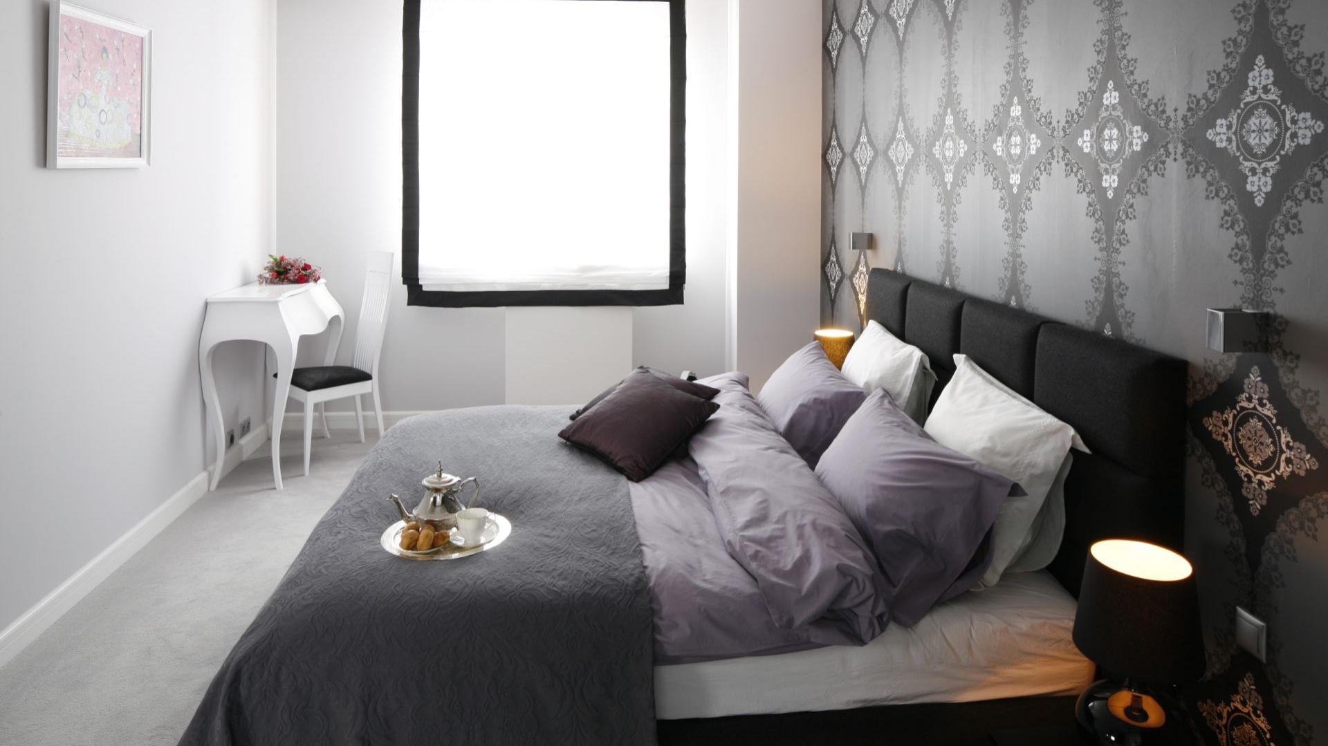 Do jasnej sypialni możemy z łatwością wprowadzić mocniejszy akcent. Tapeta z ornamentem na ścianie za łóżkiem będzie z pewnością się ciekawie prezentowała. Projekt: Magdalena Smyk Fot. Bartosz Jarosz.