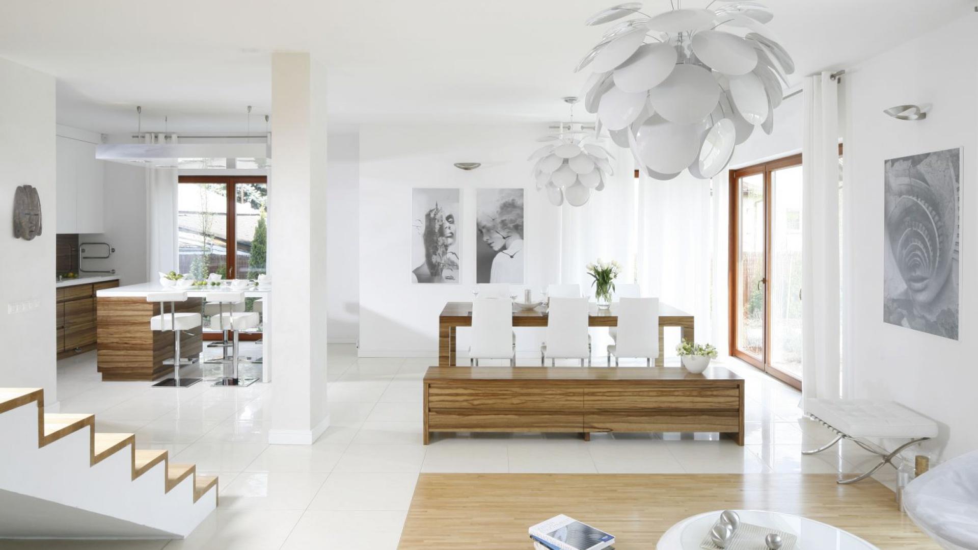 Elegancką jadalnię urządzono między kuchnią a salonem. Drewniany stół uzupełniają białe krzesła. Projekt: Agnieszka Ludwinowska. Fot. Bartosz Jarosz.