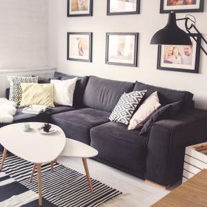 Wystrój mieszkania zainspirowany jest stylem skandynawskim. Dlatego dużo tutaj bieli, drewna, a także dekoracyjnych detali, budujących charakter aranżacji. W salonie na ścianie zawisły zdjęcia, oprawione w czarne ramki, a elegancki narożnik zdobią dekoracyjne poduchy. Projekt: Meblościanka Studio. Fot. Maua Fotografia.