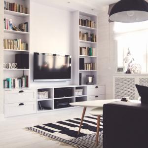 Ścianę w salonie, na której zawisł TV wykorzystano także na zamontowanie dość pojemnej biblioteczki. Projekt: Meblościanka Studio. Fot. Maua Fotografia.