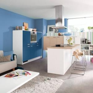 Niebieskie fronty stanowią doskonały zestaw z nieco zimniejszą w odbiorze bielą  i ciepłym wybarwieniem drewna. Całość aranżacji otwartej strefy dziennej dopełnia niebieska ściana, która znajduje się nie tylko w kuchni, ale i w salonie. Fot. Pino.